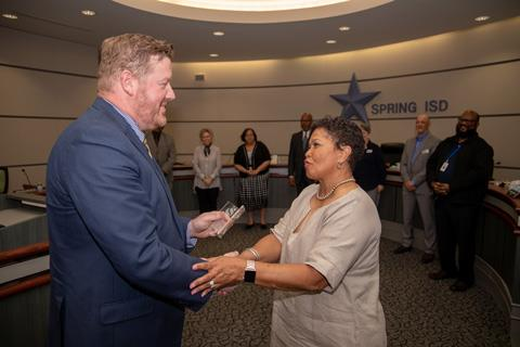 Special Education Coordinator Christopher Gereke, from left, is congratulated by Spring ISD Board of Trustees President Rhonda Newhouse for his induction into the Crisis Prevention Institute's Hall of Merit.