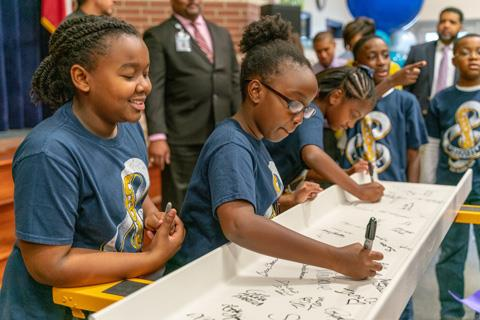 Future Middle School #8 students Sydnie Harrison, Pauline Ocharo and Kamryn Lincoln sign the beam for their new school, while LeAnderay Collins and Quinten Starks wait their turn